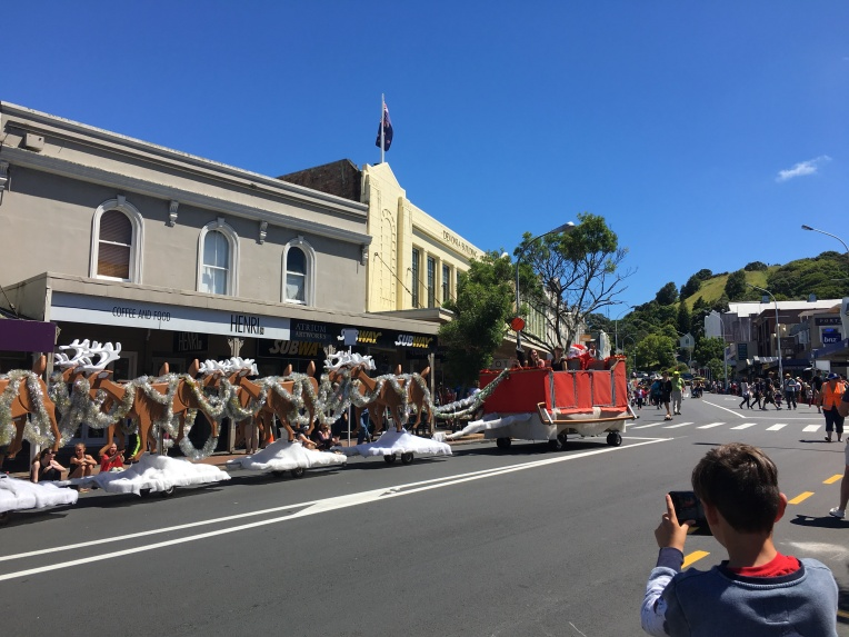 Santa arrives at the Devonport Christmas Parade, traveling down Victoria Street, the main drag in our town. Mt. Victoria in the background.
